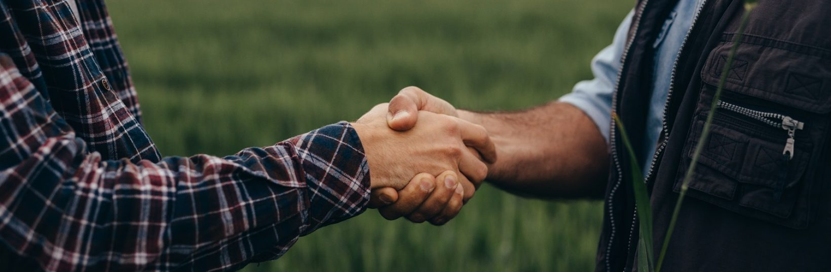 close up of two man handshake on field